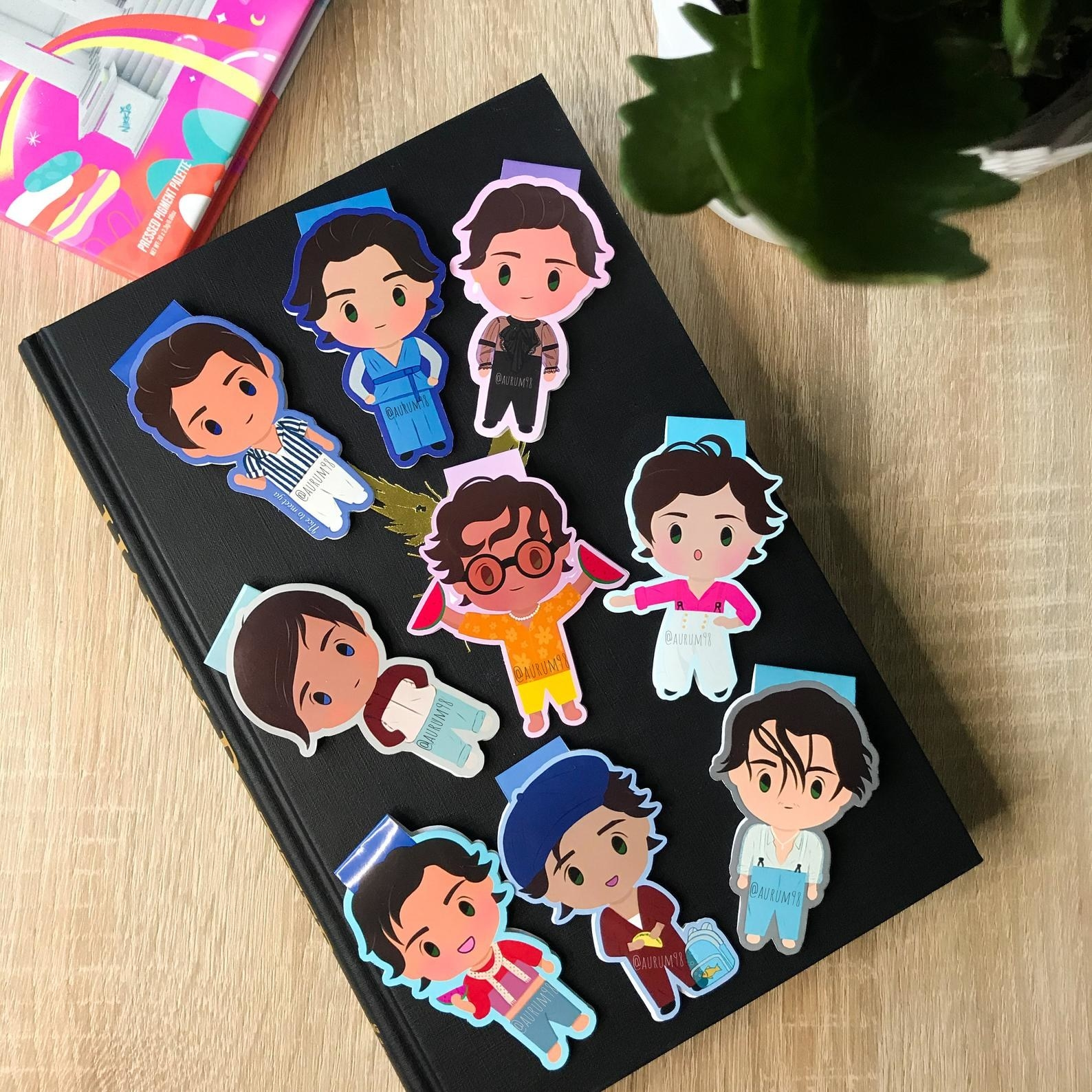 Bookmarks shaped like cartoon versions of Harry Styles in different outfits
