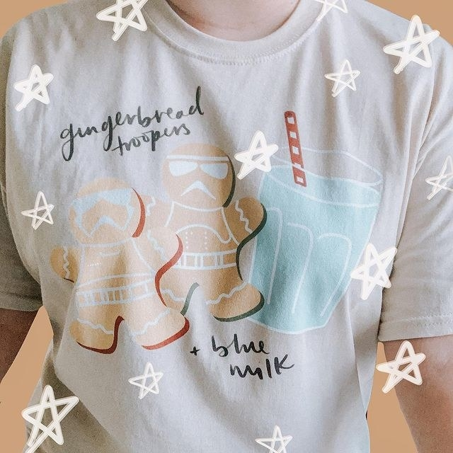 a light tan tee with two gingerbread storm troopers on it and a glass of blue milk
