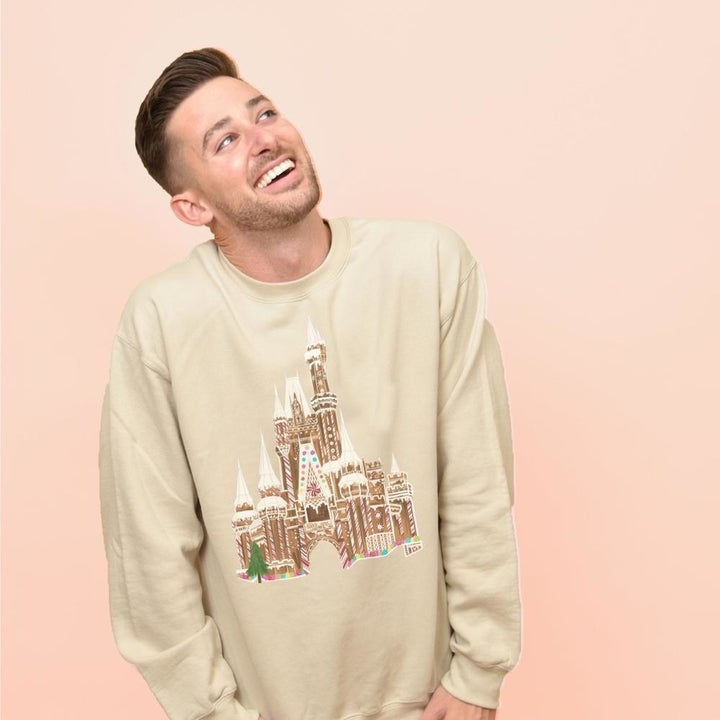 a model in the tan sweatshirt with the gingerbread castle on it