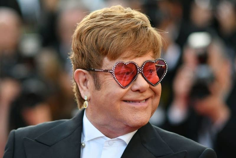 "Elton John at the screening for ""Rocketman"" in 2019, smiling while wearing heart-shaped glasses"
