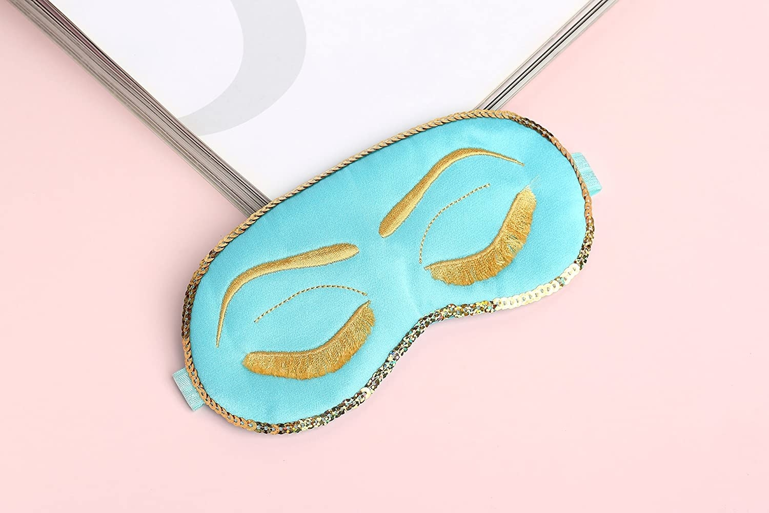 The aqua mask with gold sequin trim and gold embroidery to look like eyebrows and eyelashes