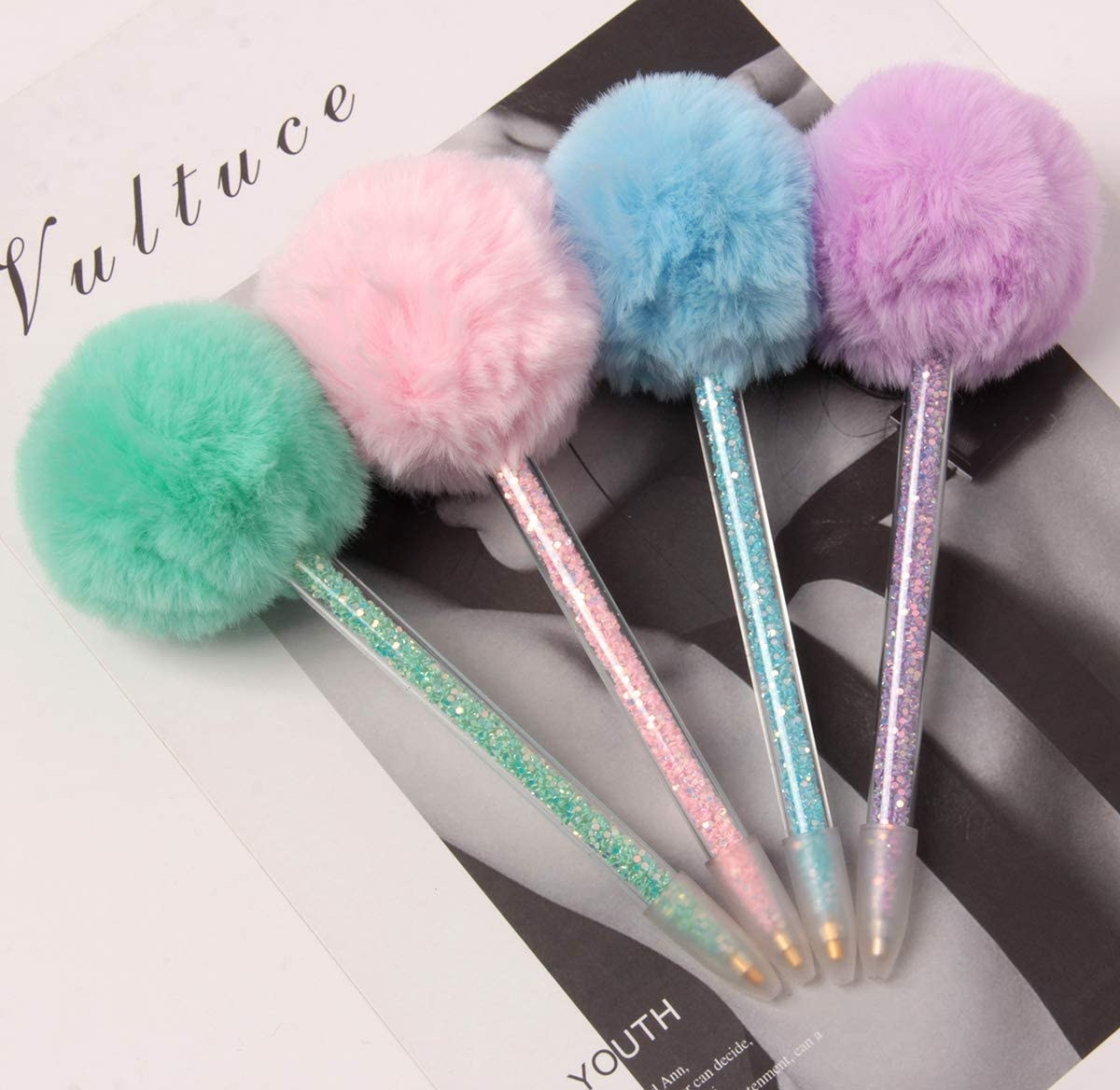The pens in green, pink, blue, and purple with beads in the pens and a faux fur puff ball on top of each