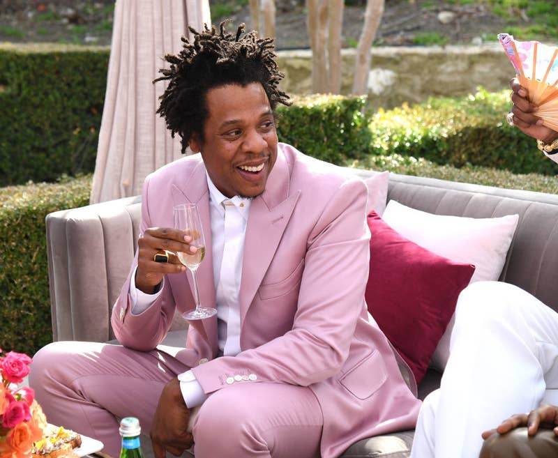 Jay-Z at the Roc Nation brunch, wearing a bright colored suit and drinking champagne