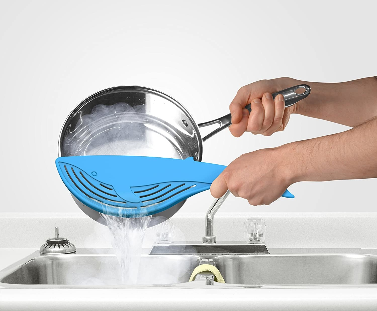 A blue whale-shaped strainer held against a pasta pot to drain water