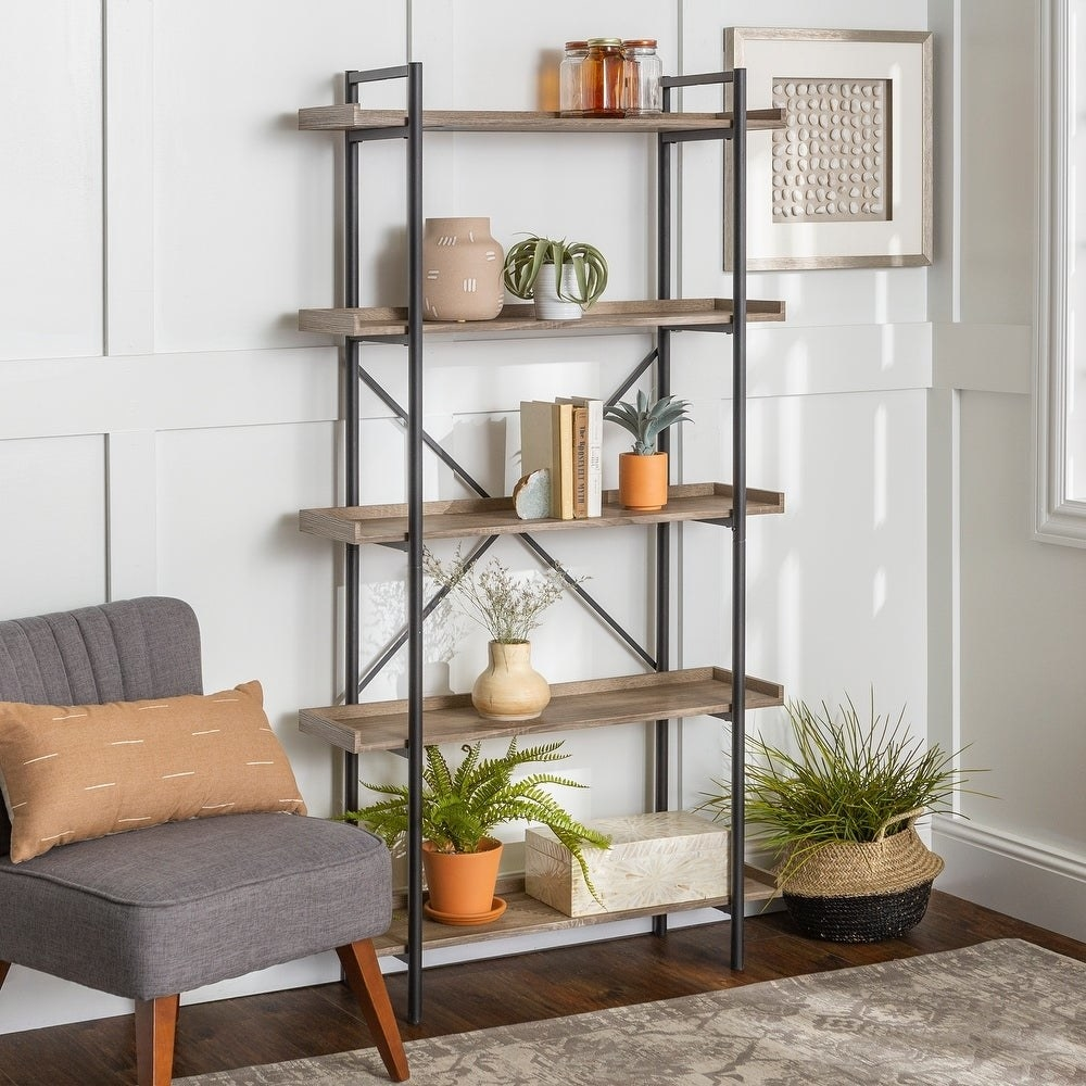 The five-tier bookshelf holding books, plants, and decor