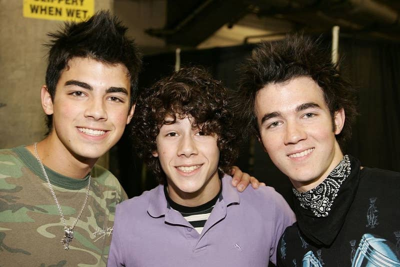The Jonas Brothers posing backstage as a Radio Disney event in 2006