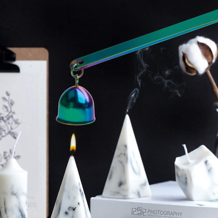 A rainbow tinted candle snuffer over a lit candle