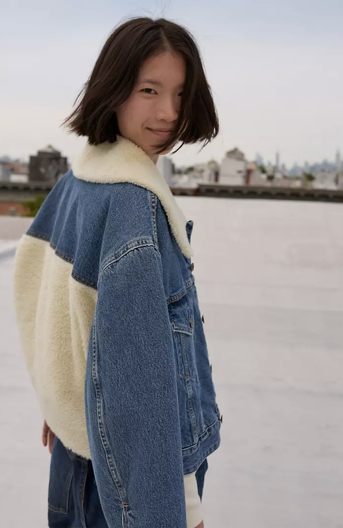 model wears denim jacket with furry back and lapel