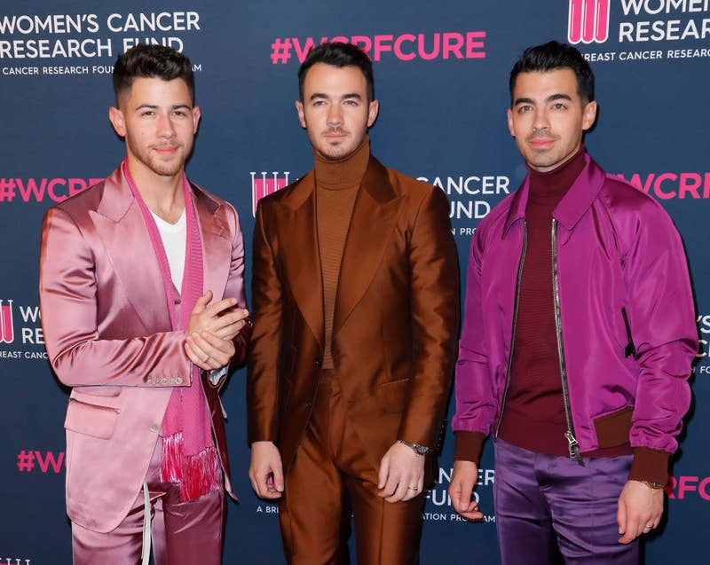 The Jonas Brothers posing on a red carpet at The Women's Cancer Research Fund's Unforgettable Evening in 2020