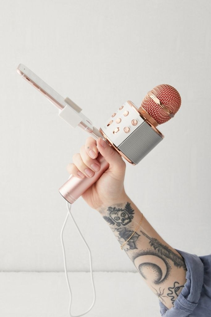 a model's hand holding the rose gold karaoke microphone