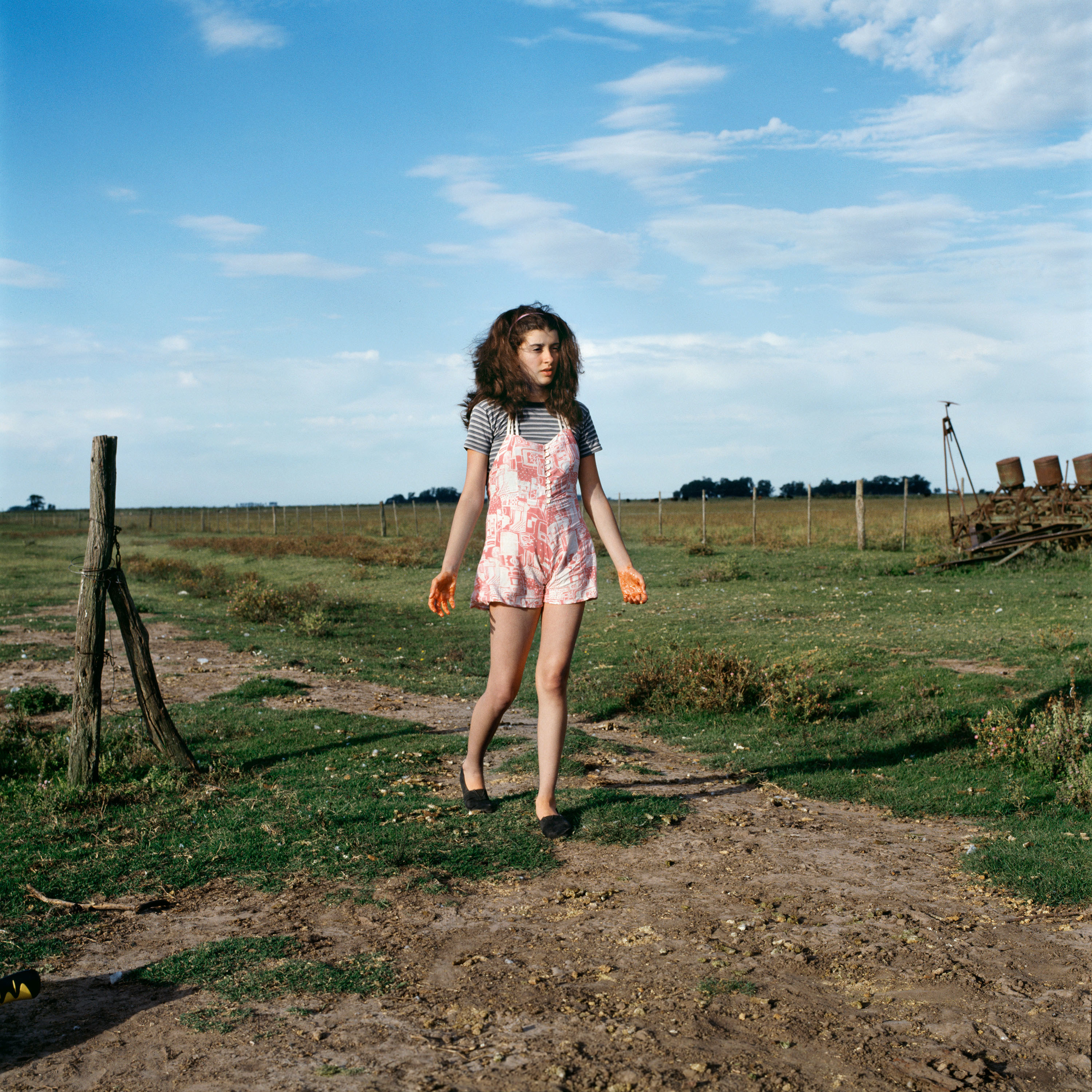 A girl in a striped shirt and pink romper walks through a field under a blue sky