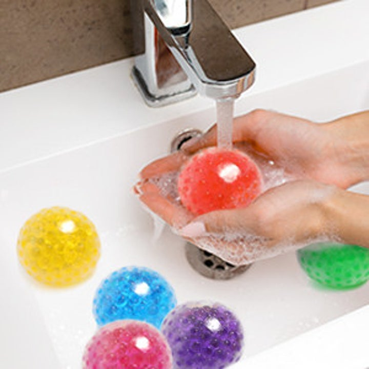 a model washes the sensory stress balls in a sink