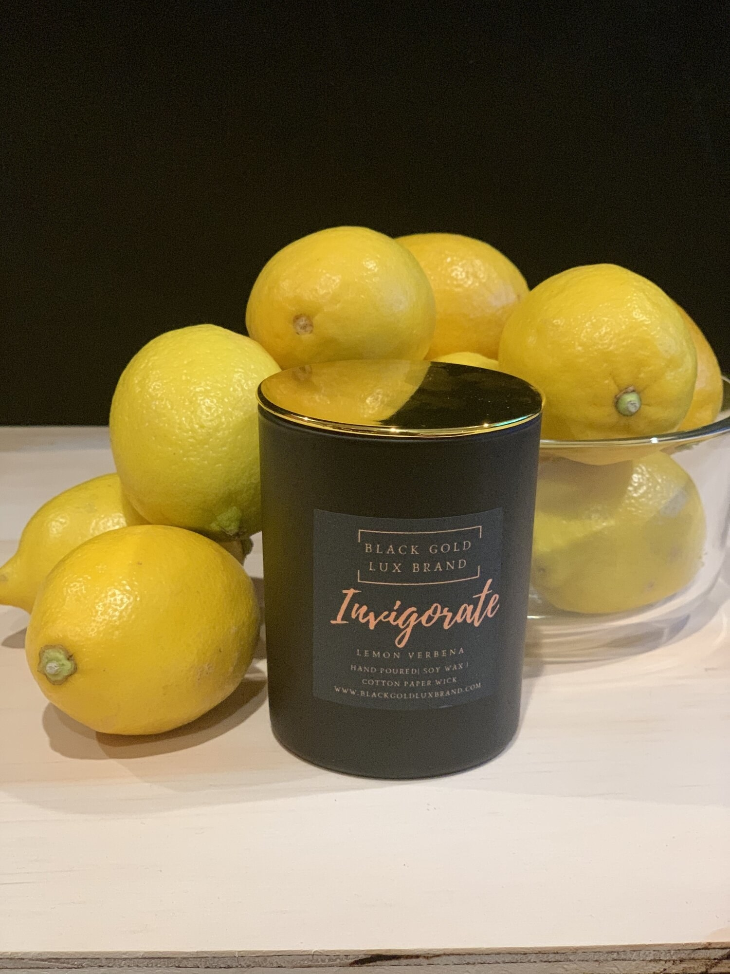 The Invigorate Candle surrounded by a bowl of lemons