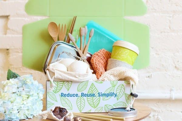 the box with reusable utensils, coffee cup, dryer balls and other items