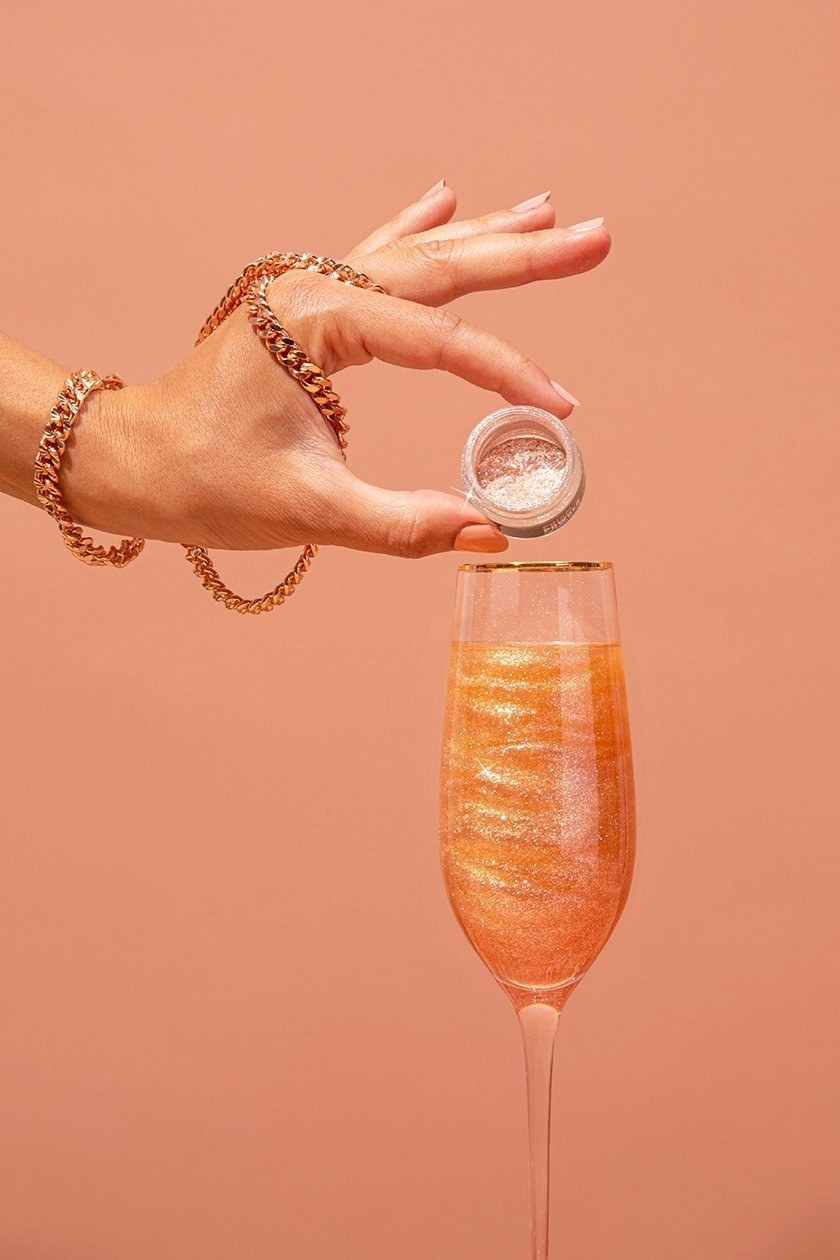 person pouring glitter into a champagne glass with an orange drink that looks sparkly