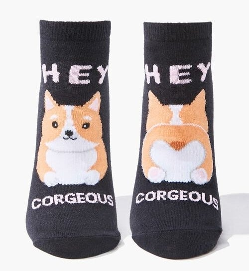 """A pair of knit ankle socks featuring """"Hey Corgeous"""" text and split graphics of a corgi's front and backside"""