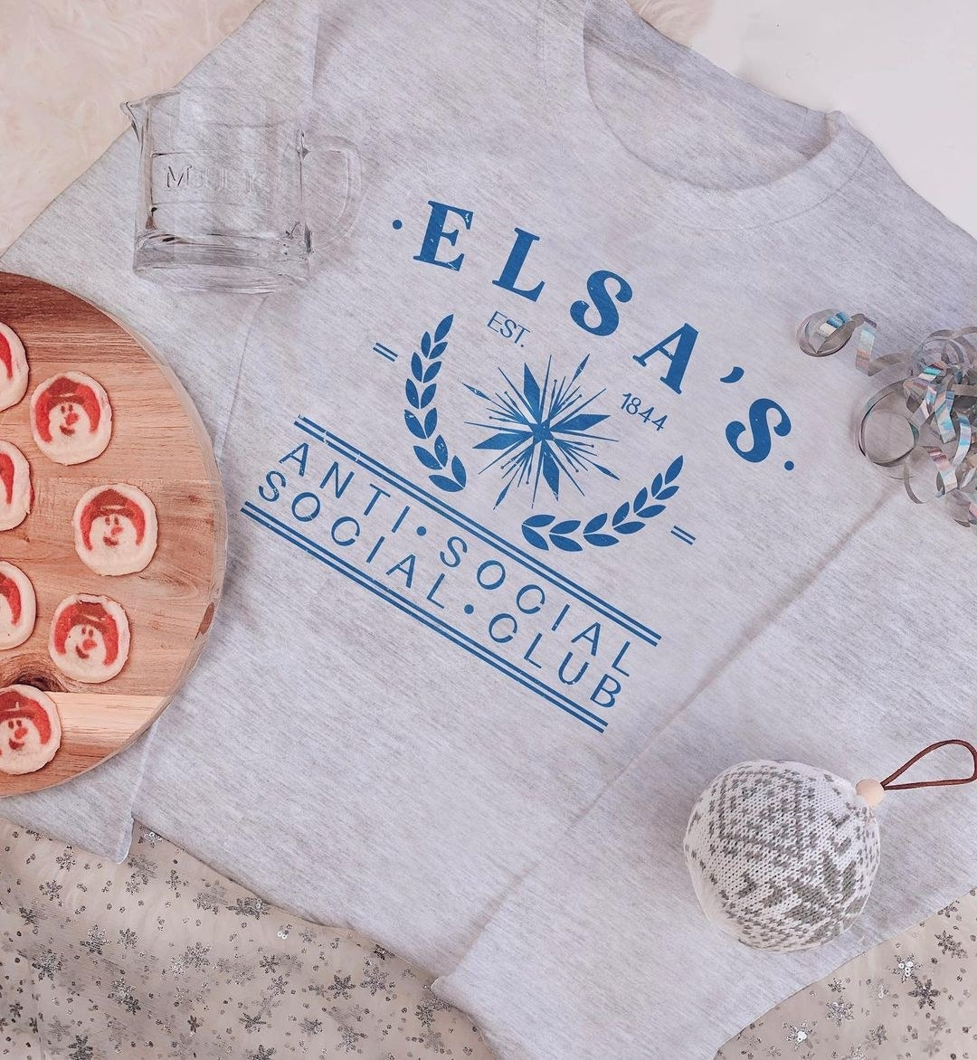 "a gray sweatshirt with a snowflake on it and the word's ""elsa's anti social social club"""