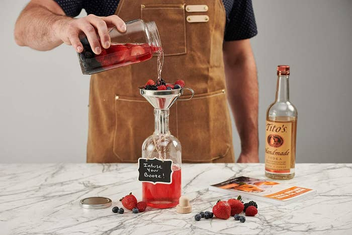 person pouring a berry concoction into a funnel with berries