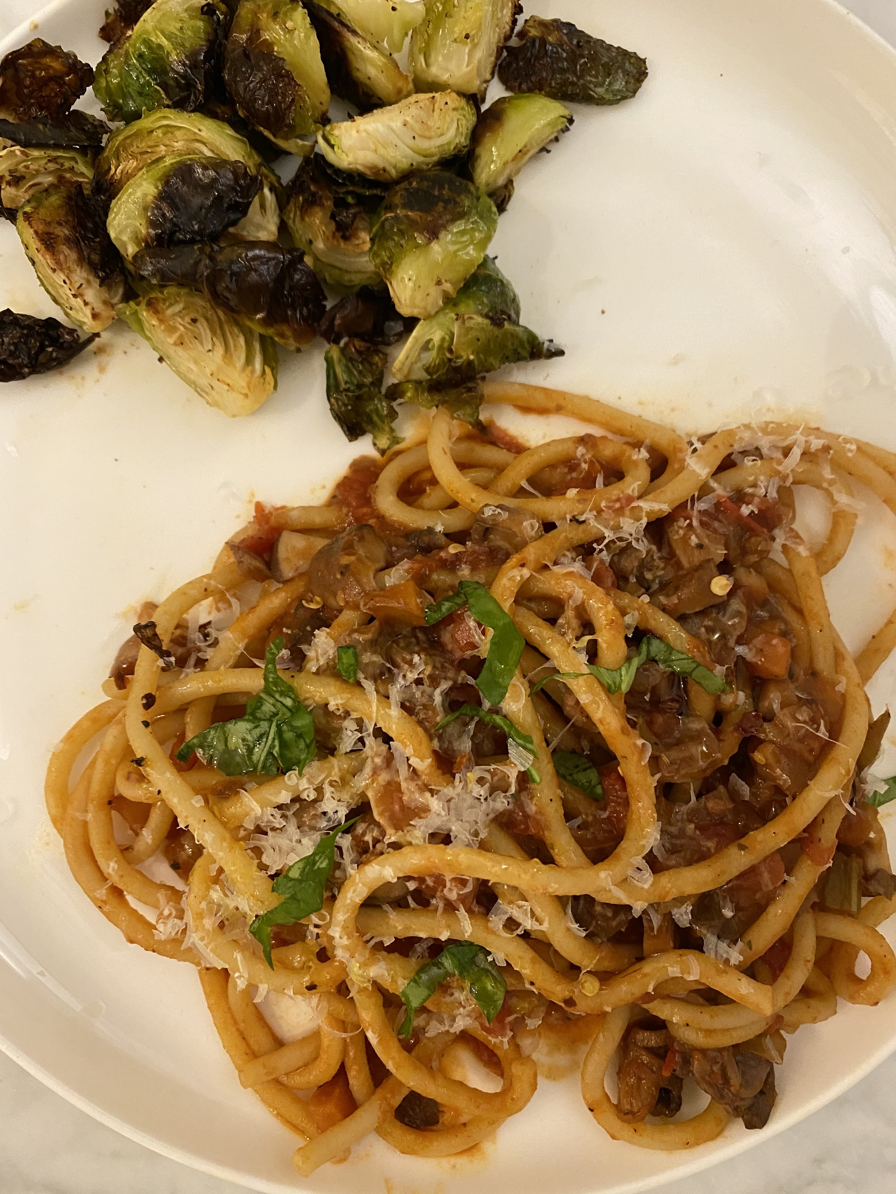 A plate of spaghetti in mushroom Bolognese sauce and a side of roasted Brussels sprouts.