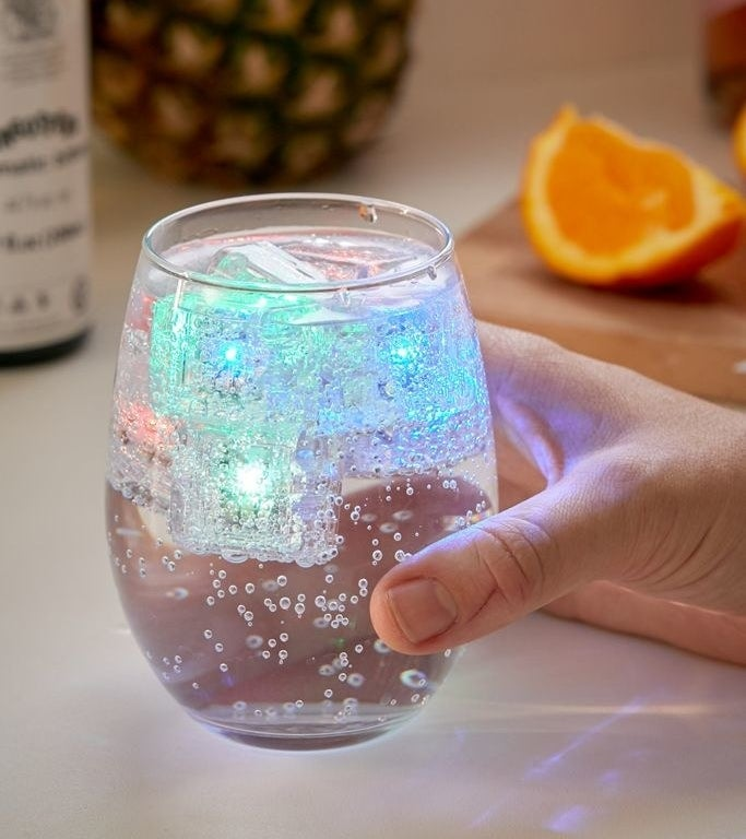 the cubes lit up different colors in a glass