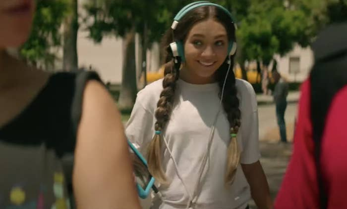 Maddie as Music in long pigtails and a pair of headphones over her ears