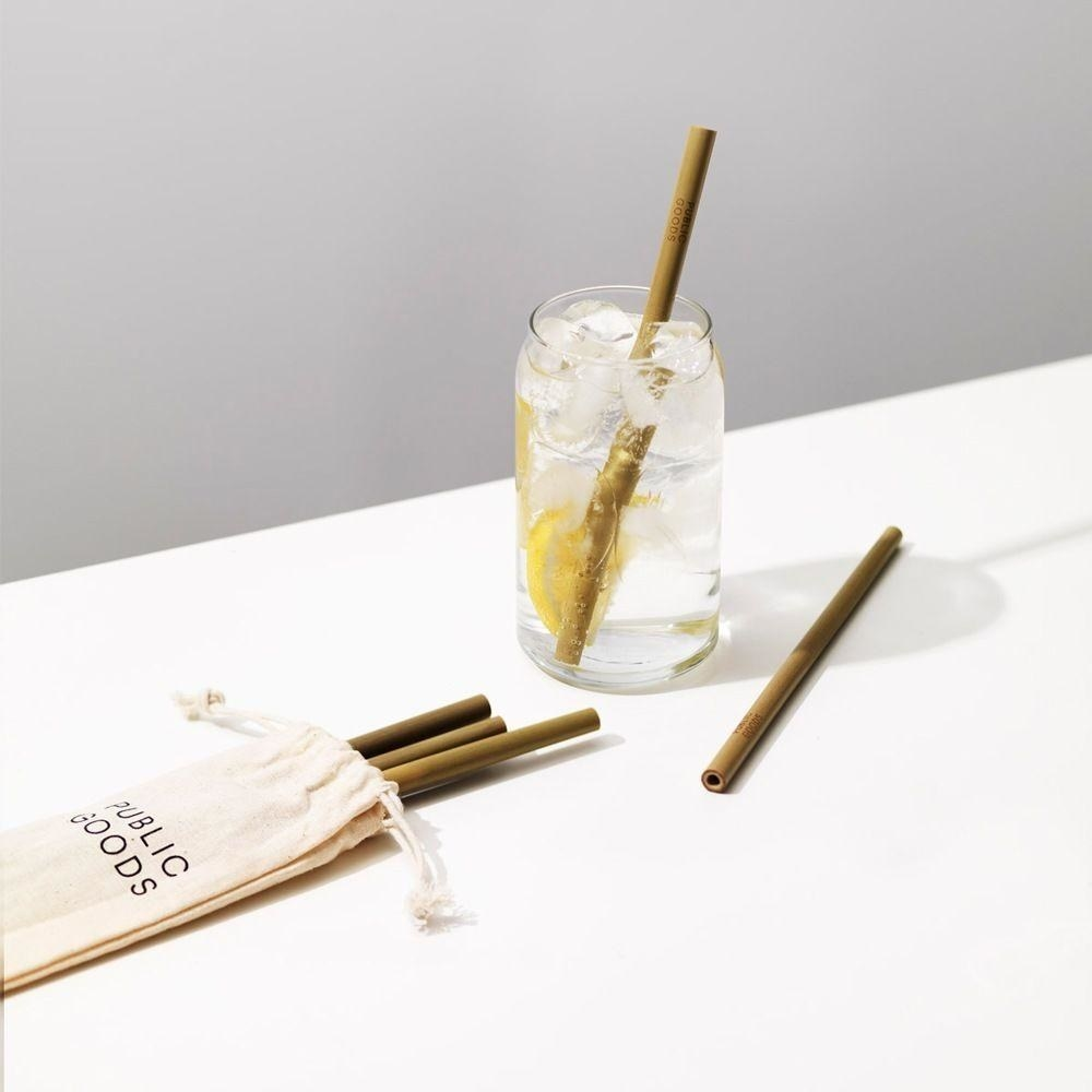 a bamboo straw in a glass of ice water and a few more bamboo straws lying around it
