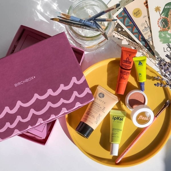 an unpacked Birch box with makeup, brushes, and skincare products