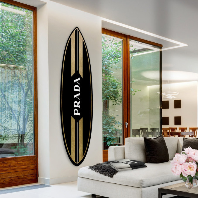 """gold and black surfboard wall art with """"Prada"""" on it in a living room"""
