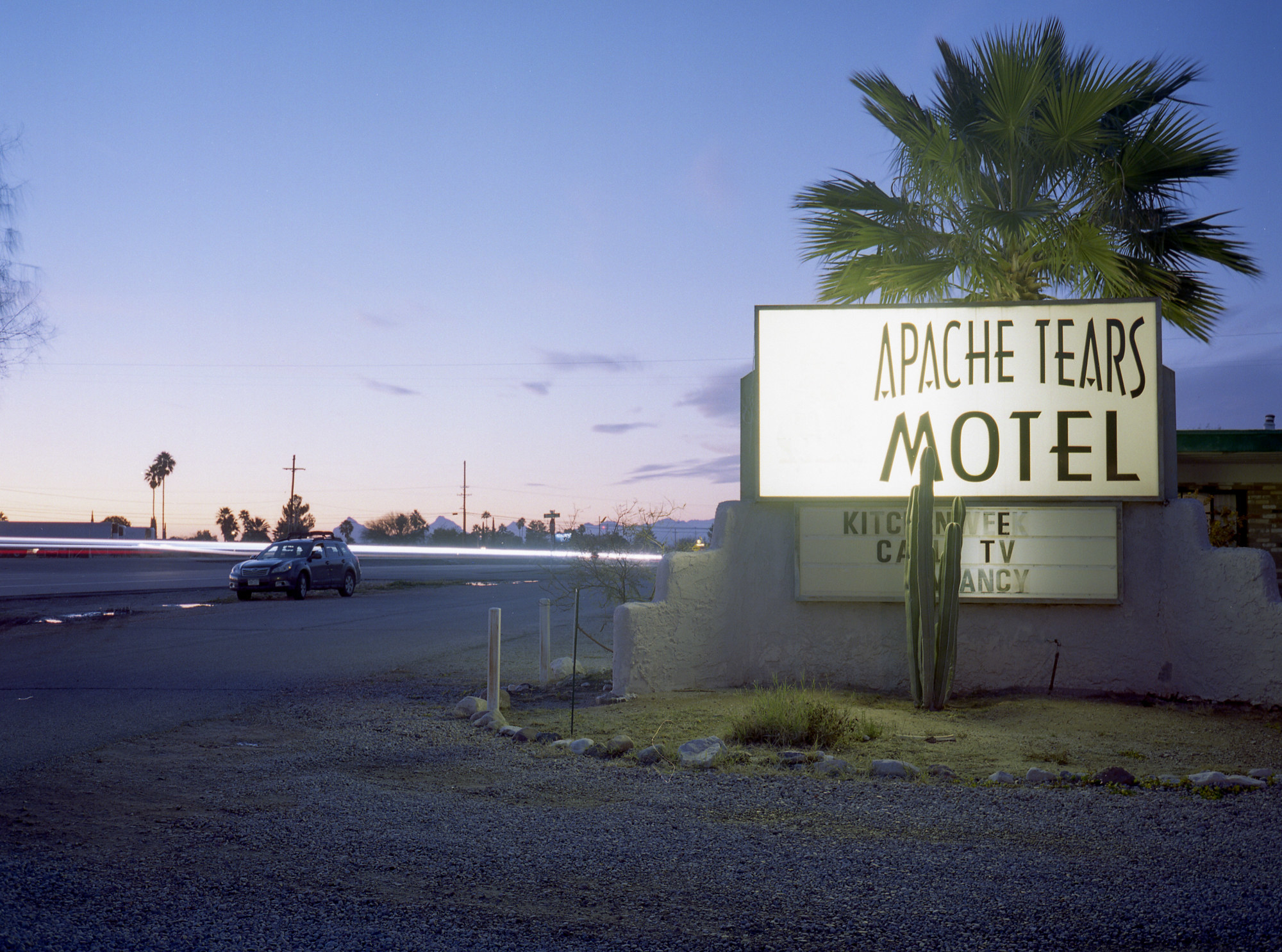 """A car parked to the left in an empty lot, a sign that reads """"Apache Tears"""" underneath a palm tree."""