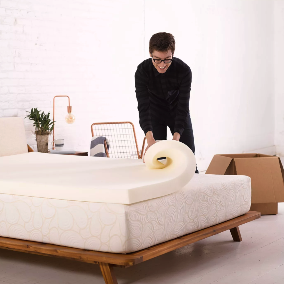 Person is rolling a mattress topper on a mattress