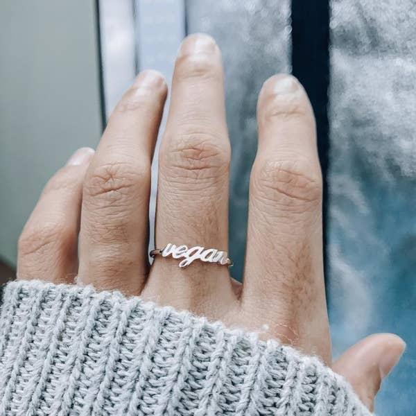 orta parmağında vegan yüzüğü olan bir el