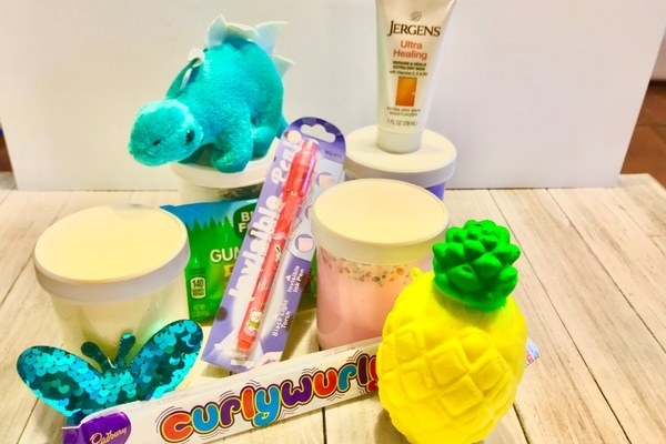 three jars of slime, a pen, sequin butterfly plushie, and other toys
