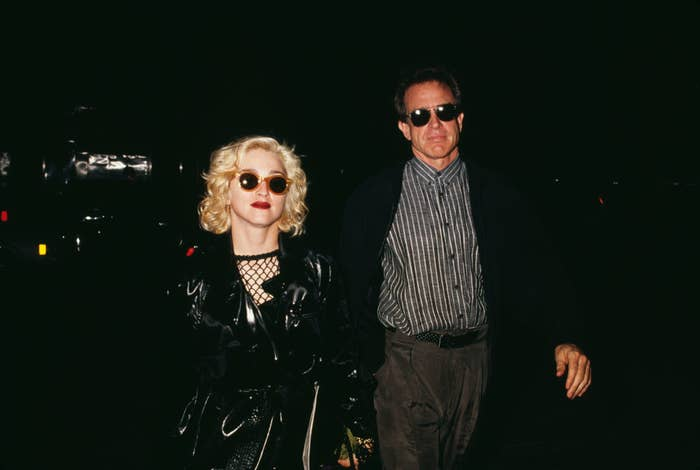Madonna and Warren Beatty walking down the street at night in sunglasses, 1990