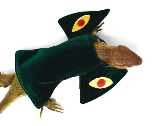 A plastic lizard toy wearing the dark green mini dress, which has billowy sleeves with eyes on them