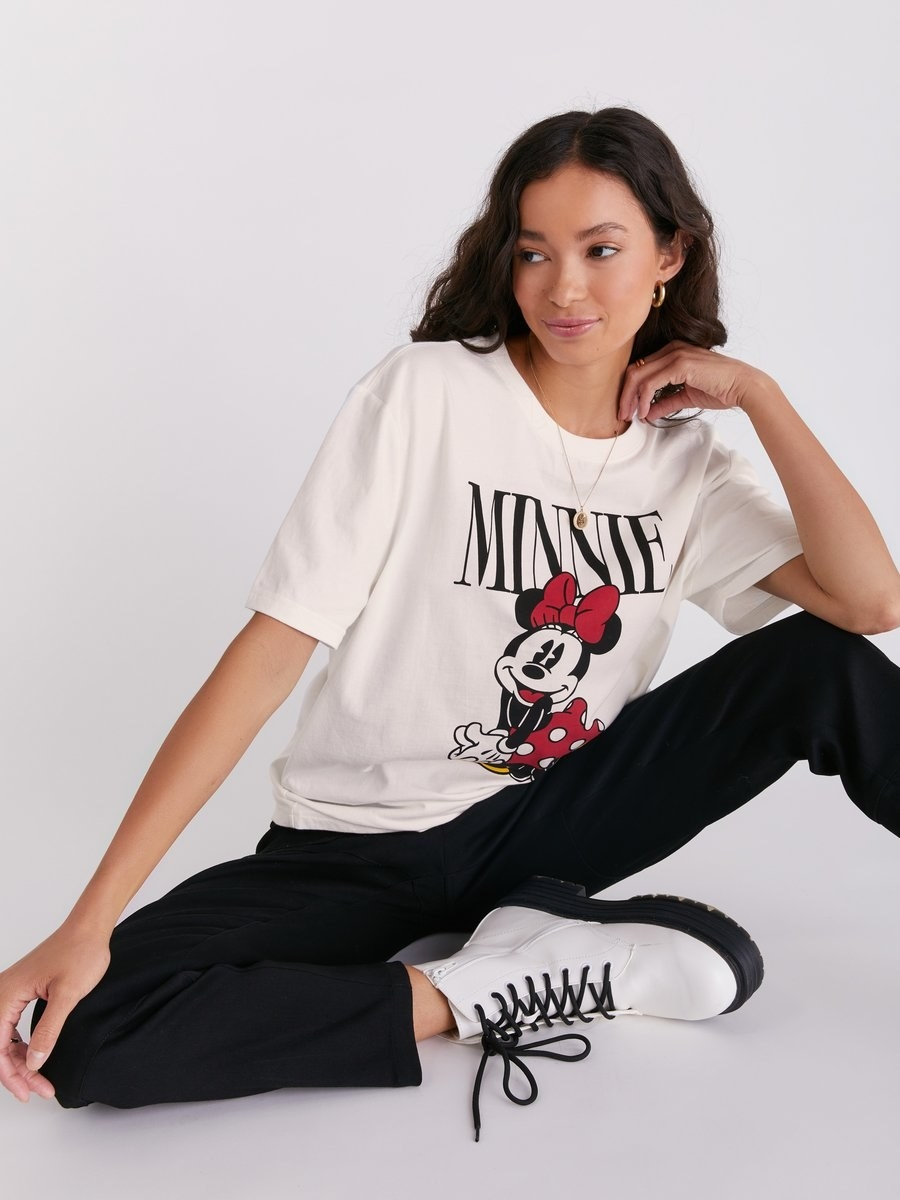 "a model in a white oversized tee with the words ""minnie"" on it and an image of minnie mouse"