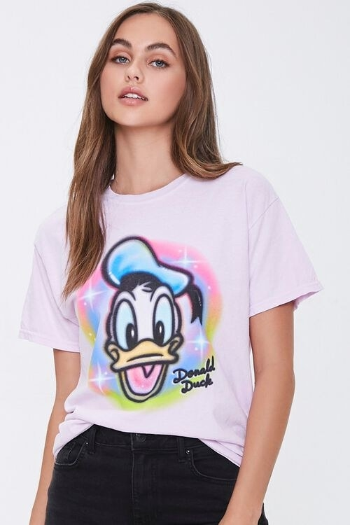 a model in a lavender tee with donald duck on it