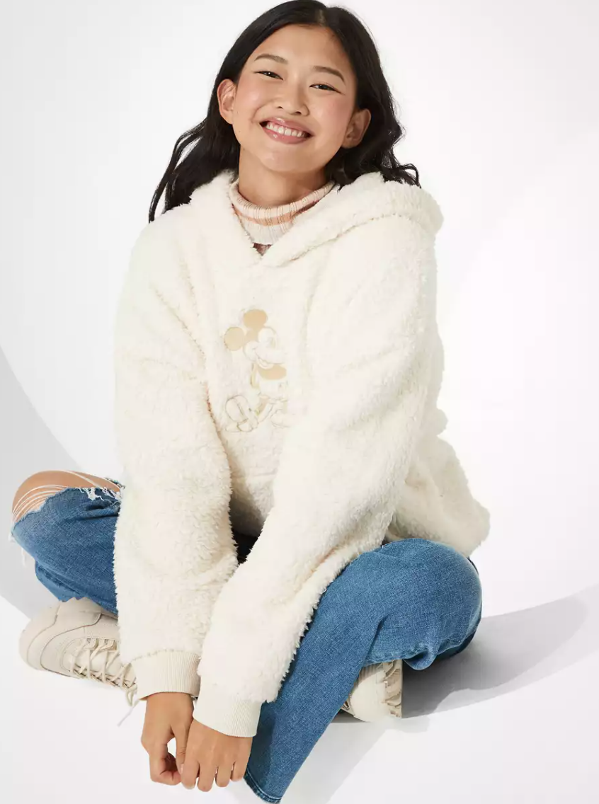 a model wearing the fluffy white sweatshirt with mickey embroidered on the middle