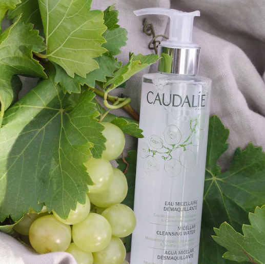 A bottle of the product on a background with leaves and grapes