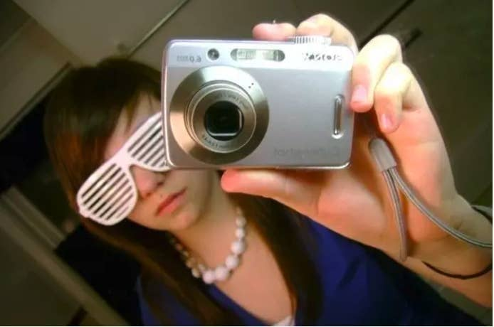 Photo of a girl taking a mirror selfing wearing shutter shades and pointing the camera in front of her face toward the mirror