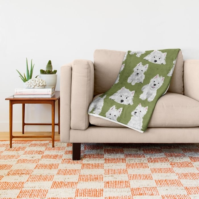 Green throw blanket with westies on it shown in a living room setting