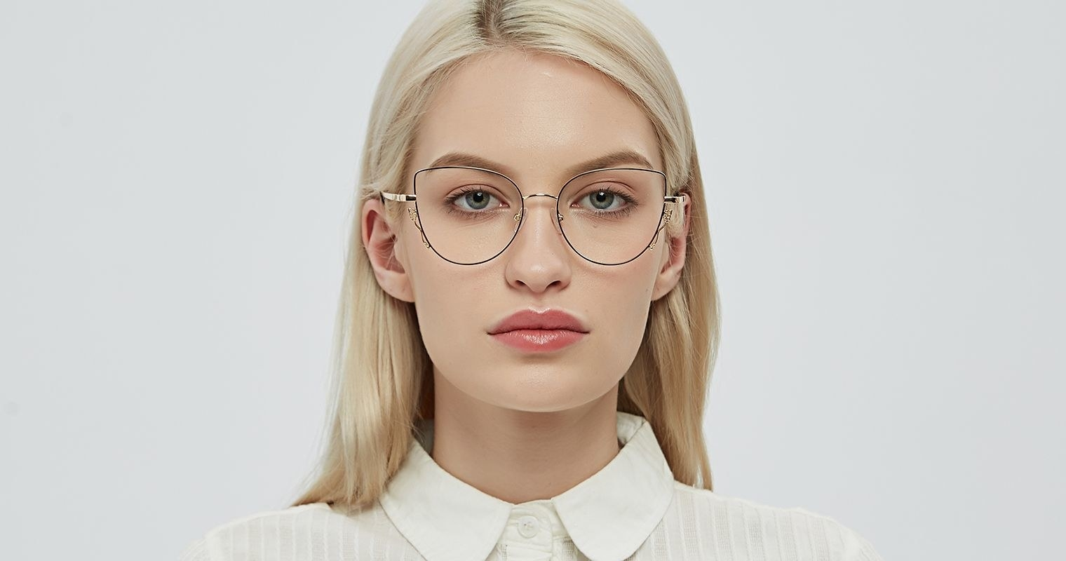 model wearing large cat eye glasses in black and gold