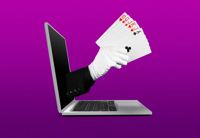 An illustration of a gloved hand holding playing cards extends from a laptop screen, as if by magic