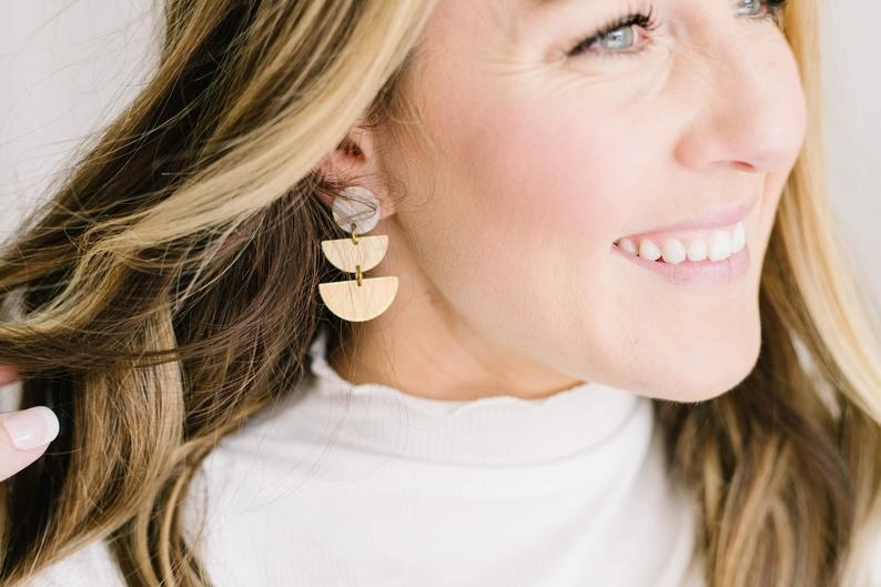 Model wearing double half-moon earring on right ear