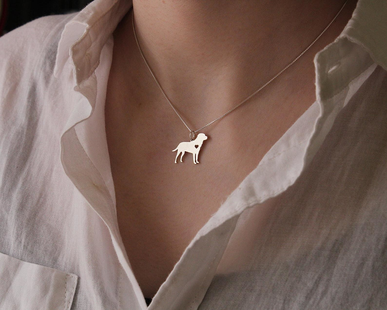 Person wearing a silver necklace with a labrador pendant