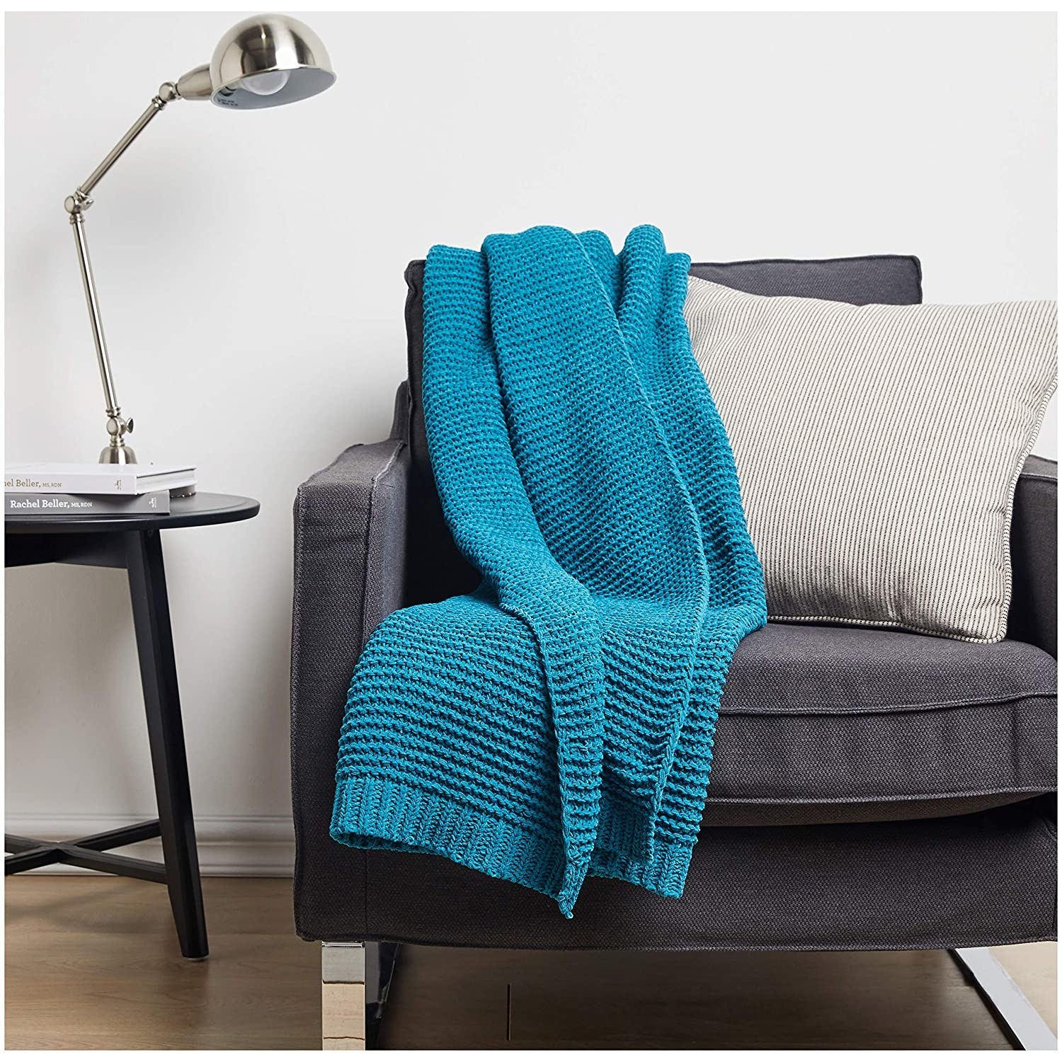 The teal chenille blanket draped on a grey sofa.