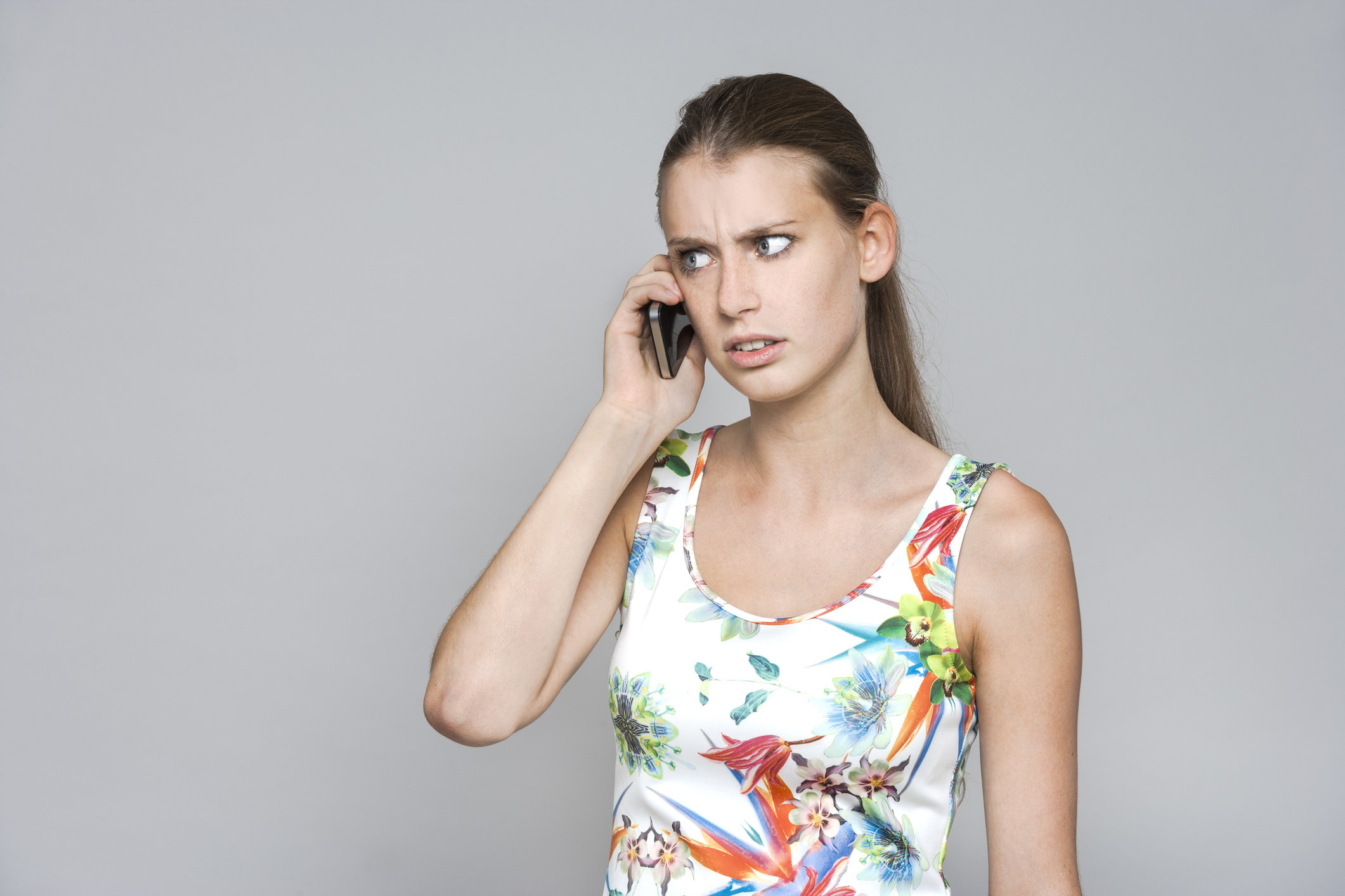 A photo of a woman looking confused on a phone