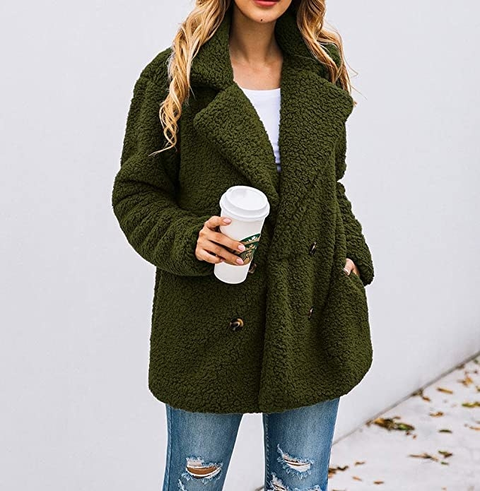 model wearing the teddy jacket with buttons, large lapel, and green color