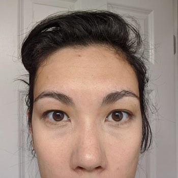 The same reviewer wearing the concealer, which has brightened the under-eye area