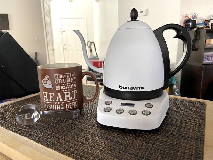 The electric kettle on a counter in white.
