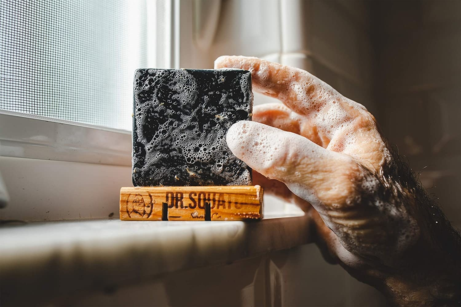 hand reaching for sudsy bar of soap